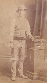Full shot of man (Aaron Sherritt). He wears a hat, waistcoat and cummerbund and stands with his left arm resting on a podium. A book is placed on the podium.