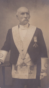 A portrait of a man, who is older in age. He is in uniform and has a handlebar moustache.