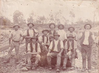Sepia toned photograph of a group of 10 miners, some sitting on a log and some standing behind, with a dog in front of what appears to be an open cut mine.