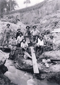 A sepia photograph of eleven miners from the Three Mile Miners standing and sitting around a plank of wood near a water race. In the background is a dirt wall.