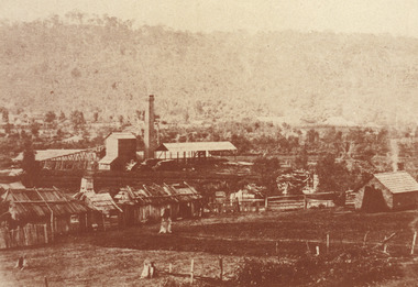 A landscape sepia photograph of a cleared landscape with very few trees and vegetation in the background. In the foreground, there is a clearing of land before a collection of wooden huts and tree stumps. Beyond this, the Rocky Mountain Mine can be seen in the distance with number of wooden buildings and a towering brick chimney.