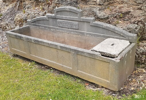 On the right end of the trough there is a small division that has a removable concrete cap that covers the opening. There is a depression in the centre of the cap that possibly once had a handle fitted there. This end of the trough has several chipped areas of damage. Inside the larger side of the trough there are colour changes in the concrete that are likely to have been caused by different levels and types of contents.