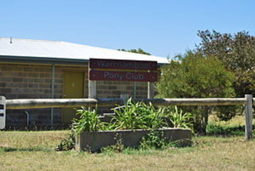 Horse trough is in front of the Warrnambool Pony Club sign. There is a grey brick building in the background. The trough is filled with green leafy plants.  The photograph was published in Wikimedia Commons, on a page called Bills Horse Troughs.