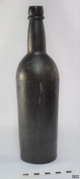Black glass, cylindrical, bulbous neck. A narrow white line is down one side.