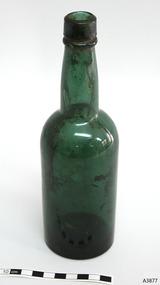Blue green bottle, tall, sediment inside