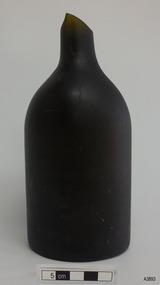 Bottle is black glass, has broken mouth, short neck, broad shoulder, body tapering slightly inwards