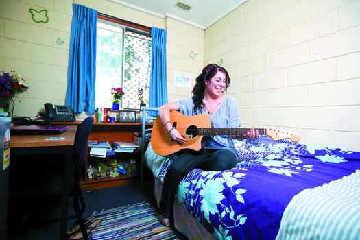 A woman plays a guitar on a bed