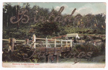 Colour image of a wooden bridge crossing a river. There is a child standing on the bank of the river in the foreground. On the far side of the bridge stands a small house which is surrounded by a wooden fence. In the background is a forest. Birthday Greetings has been written in glitter across the image. On the reverse of the postcard is a handwritten message in black ink. In the upper right hand corner a postage stamp has been removed.