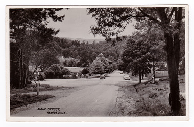 An early black and white photograph of the Main Street in Marysville, Victoria. In the background can be seen the Australia Hotel which became The Cumberland Hotel. Also in the background can be seen a sign with an arrow pointing to the Mary-Lyn Guest House.