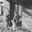 Girl and boy stand at an external door way of a brick house, near a corner.  The boy pats a dog who is wagging its tail with its rear view to the camera.  Brick rubble surrounds the exterior