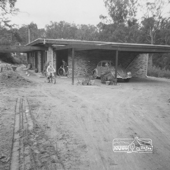 A large unclutterd dirt driveway leads to the brick house and car port with VW Beetles reverse parked.  Two boys ride two-wheeler bikes