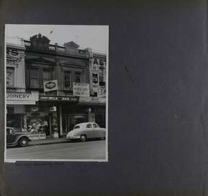 1 photo on page - view of old-style double storey shops with old cars parked out the front.