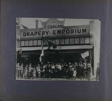 One photo of a crowd in front of a shop named as T Grogan's Drapery Emporium.  People are dressed in early 20th century clothes.