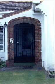 """Brown brick arch entrance to porch with cast iron work gate set in rendered house exterior, with lamp light on the left top corner.  House number """"5"""" in white halfway up the arch."""