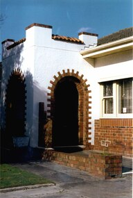 Fortress-like central white entrance porch with 2 open brown brick arches with steps, decorative glass in the top left sash window and a brown brick low wall over the concrete path.