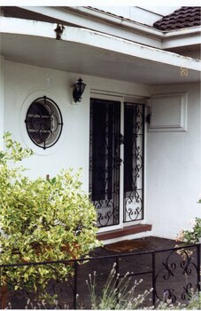 Entrance porch with round window circled by black metal and lace-like grating, which matches the decoration of the black double outer doors (in front of double glass doors) to the right of the window and the black metal decorated fence along the edge of the porch landing.  Black metal and glass light to the left of the doors and a white box with small round handle to the right of the doors.  Bushy pot plants on the left of the porch with some garden plants in front of the porch.