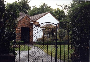 Partial front view of white house with brown brick features through decorative black metal fence.  Large brick porch with black metal door.  Well-established garden.