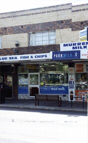 """2 storey brick shop and dwelling with several signs including the sign """"BLUE SEA FISH & CHIPS"""", with other similar shops to either side.  Large street seat on the footpath in front of the shop."""