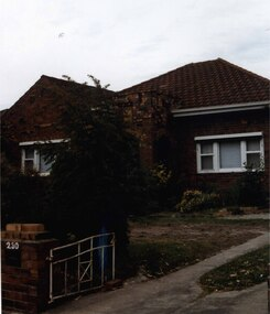 Partial view of brown brick house and matching low fence.  It has a porch with 2 arches, white framed windows, rolled up striped awnings, a white metalwork gate and broken up lawn to the left of the drive.