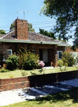 Partial front view of a mixed brown brick house with an open porch including 2 brick pillars and white trellis on the house wall, a wide tall feature brick chimney, white-framed windows and guttering matching the just visible white garage door to the right.  The established garden is behind a low brown brick fence.