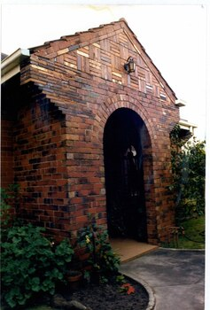 Close view of decorative arched brick porch with a metal lantern above the arch and a window on the right wall of the porch.  Garden beds each side with garden path to the porch.