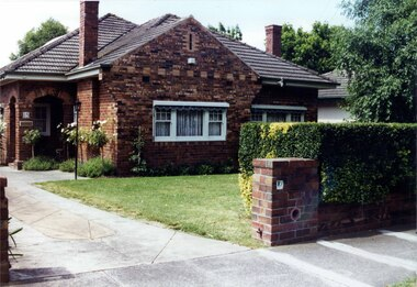 Mixed brown brick house with a double-arched porch and tall feature chimneys with brick patterns plus white windows with a concrete drive, established garden beds and lawn behind a hedge and similar brown brick fence.