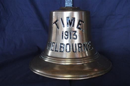 """Brass bell with indented text: """"Time 1913 Melbourne"""" in large black lettering"""