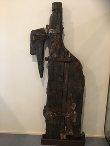 Remains of a timber rudder with 2 surviving gudgeons still bolted to it. Marks on the timber suggest the position of a a further 2 which have been lost to erosion. The top pintle survives and is still attached to timber which would have been originally attached to the ship's transom. The timber and metal of the pintle and gudgeon rudder are badly eroded and brittle.