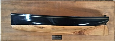 Front view of a half model of an 1890s Couta boat. Black hull above waterline; natural timber below. Mounted on panel board with a label underneath '1890's Couta Boat Victoria Aust.'