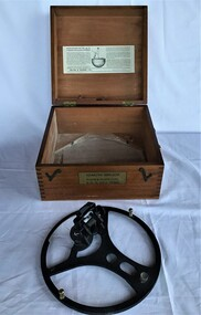 Two photographs showing the azimuth mirror circle and the timber box it is stored in. The box has instructions on the inside of the lid.