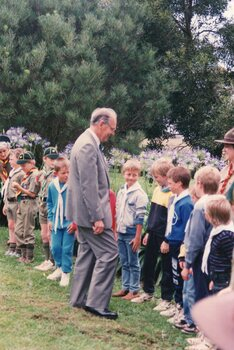 Photograph of man greeting a line of children