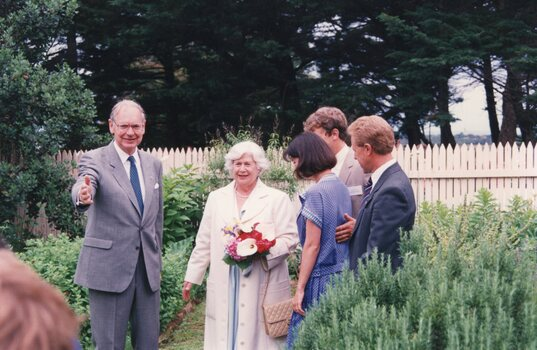 Photograph of five people standing in a garden