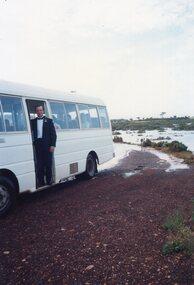 Photograph of man standing at minibus door