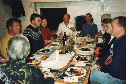 Colour photograph of a group seated at dinner