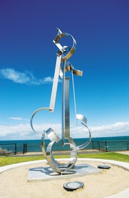 Photograph of a large stainless steel sculpture resembling clouds, wind and waves and set onto a concrete base. The base is set within a round sand area, the bay, sky and clouds are in the background.