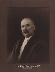 Sepia photograph of a formal portrait of a seated man, chest up, wearing mayoral robes with fur trims and jabot.
