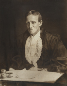 Formal portrait of seated man wearing mayoral robes with fur trims and lace cuffs and jabot, he sits at a writing desk. He has short dark hair and is clean shaven.