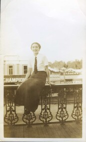 Black and white photograph of a young lady sitting on the balcony of the Club Hotel, Fraser Street, Clunes