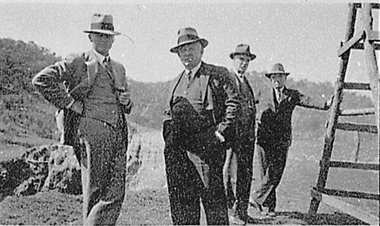 Four men standing, wearing suits and hats.