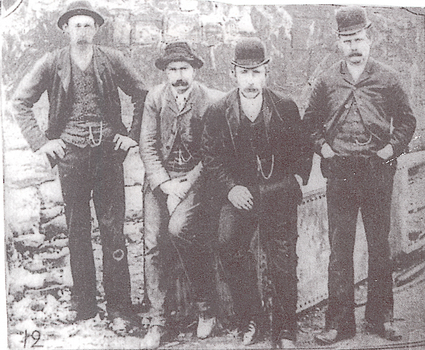 Four men dressed in trousers, jackets, waistcoats and hats posed for photo.