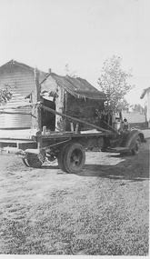 Flat bed truck carrying a small hut.