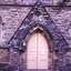 Double solid wood doors, painted yellow, shaped at the top to fit a pointed arch doorway. On the lower half of each door are two recessed rectangular panels, one above the other. On the upper half is a large panel in the shape of a pointed arch and a small panel triangular panel.