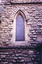 A pointed arch window set in the sandstone wall, left of the northern transept entrance. The image in the stained glass window is obscured by wire mesh. There are stones missing from the wall and other signs of water damage and weathering.