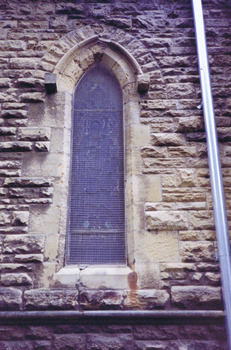 A pointed arch window set in the sandstone wall, second window to the right of the northern transept entrance. The image in the stained glass window is obscured by wire mesh