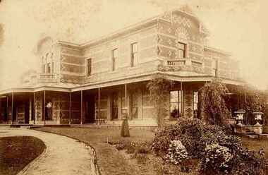sepia photo of woman standing in front of large brick house