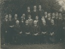 photograph: B & W photograph of a group of 21 male and female students and staff members of the Otira Methodist Home Missionary Training College, taken outdoors