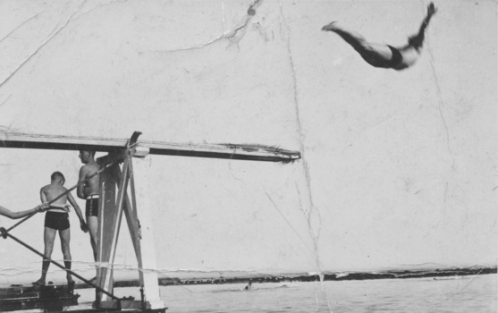 Black and white photograph of the diving board with 2 males standing  and one diving