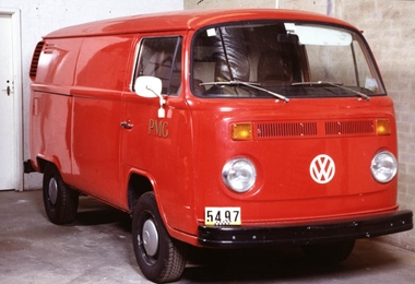Red van pictured from the front right corner, with rounded features, circular headlights and round white mirrors.