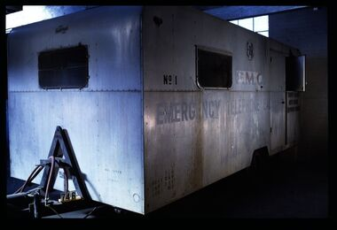 """Silver metal trailer with two rectangular windows; body of the trailer is riveted together and painted with the words """"PMG/EMERGENCY TELEPHONE EXCHANGE"""""""