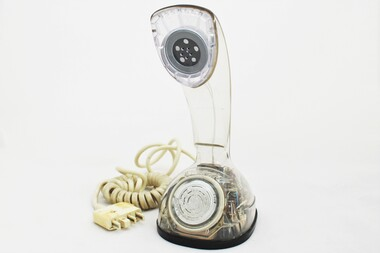 Clear plastic telephone with dial underneath long stemmed handle; colourful electrical wires visible within.